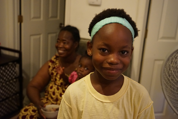 Grace Angama, 9, in the foreground. Her mother, Giselle, 51, and Giselle's granddaughter, Ellary, 2, are seated in the background at their apartment in South Philadelphia. (Harvey Finkle)
