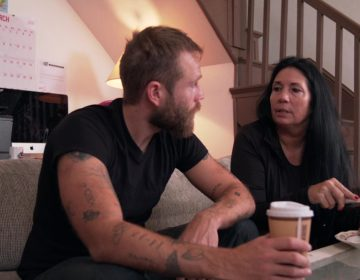 Bearded and tattooed man (left) dark haired woman (right) sit on a couch