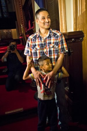 Javier Garcia Flores and his son Javier, 5, wait inside the sanctuary of the First United Methodist Church on Arch Street in Philadelphia, before Flores will take his first steps outside the church since November of 2016. (Kimberly Paynter/WHYY)