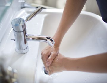 A person, out of frame, washes their hands in a sink; white sink, silver fixture