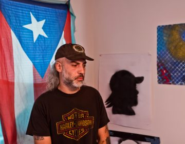 A bearded man in a Harley Davidson tshirt and a hat stands in a home; the flag of Puerto Rico hands in the window behind him