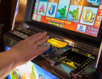 A woman plays the slots at Hollywood Casino at Penn National Race Course in Dauphin County, Pennylvania. (Lindsay Lazarski/WHYY)