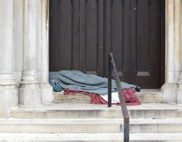 With only an elbow visible, a homeless person sleeps in a door way at a Center City Church (Tom MacDonald, WHYY)