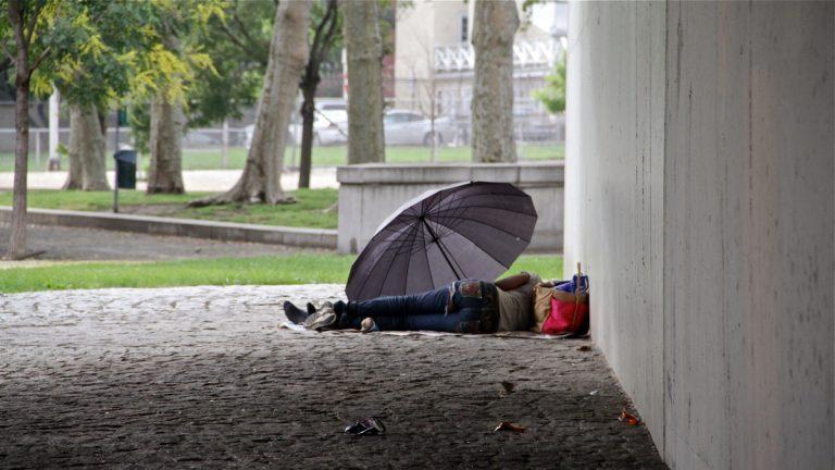A homeless person is shown sleeping under an umbrella.