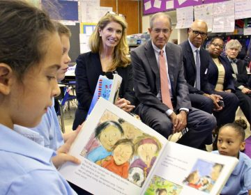Comcast CEO Brian Roberts and his wife, Aileen (center), listen as Hackett School third-grader Madison Boudreaux reads. Through their foundation, the Robertses donated $450,000 to put books in Philadelphia public school classrooms. (Emma Lee/WHYY)