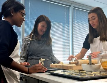 Three female high-schoolers working in a test kitchen, baking equipment, rolling pin on counter