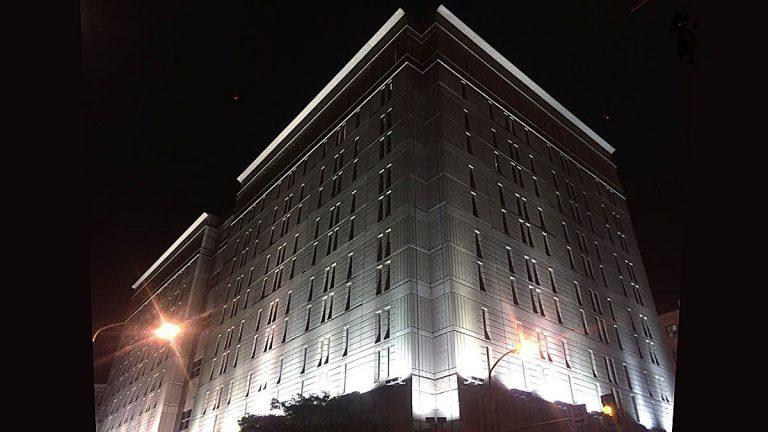 Bright lights illuminate an imposing grey stone building against a dark night sky