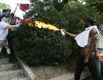 A counter demonstrator uses a lighted spray can agains an Alt Right demonstrator at the entrance to Lee Park in Charlottesville, Va., Saturday, Aug. 12, 2017.