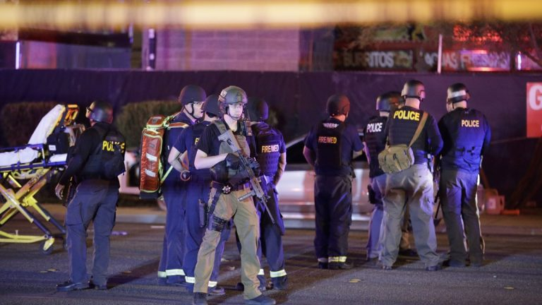 Police officers and medical personnel stand at the scene of a shooting near the Mandalay Bay resort and casino on the Las Vegas Strip