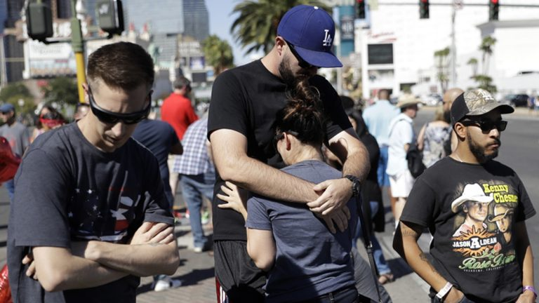 Reed Broschart, (center), hugs his girlfriend Aria James on the Las Vegas Strip in the aftermath of a mass shooting at a concert Monday, Oct. 2, 2017, in Las Vegas.