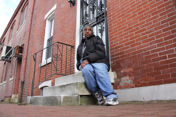 A woman sits on the concrete steps in front of her Philadelphia rowhome