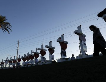 A woman passes crosses set up to honor those killed during the mass shooting in Las Vegas.
