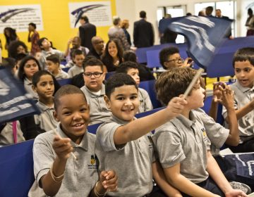 Mastery Cramer Hill Elementary school students Marvell Rivera and Jadhiel Tineo wave flags at the school dedication in Camden Tuesday morning. (Kimberly Paynter/WHYY)