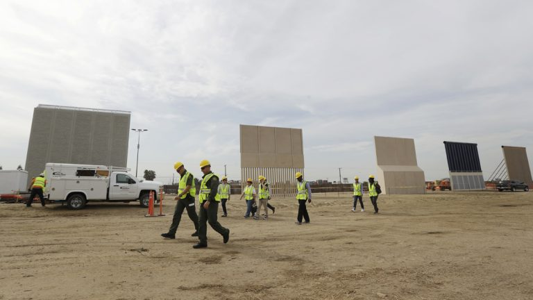 People pass border wall prototypes as they stand near the border with Tijuana, Mexico, Thursday, Oct. 19, 2017, in San Diego.