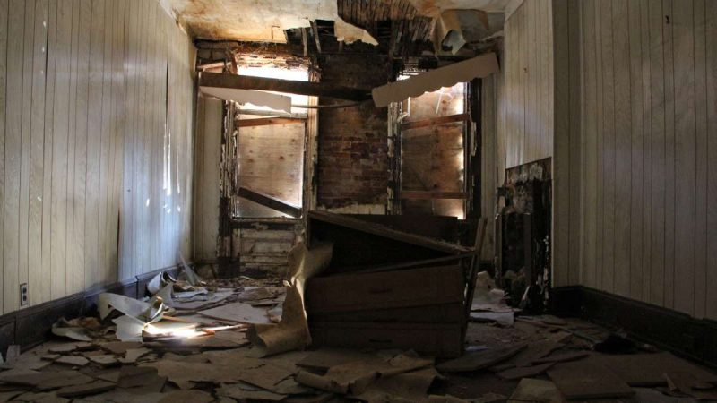 Shafts of light penetrate the boarded windows in the living room of 753 Walnut St. (Emma Lee/WHYY)