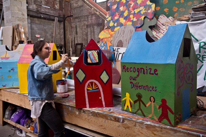 Spiral Q apprentice Laura Beery paints houses for Peoplehood parade participants to wear on Saturday. (Kimberly Paynter/WHYY)
