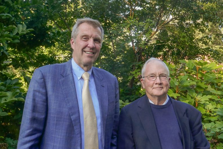 Two men pose for a picture, both in similar hues of purples