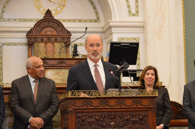 Tom Wolf at the podium in Philadelphia City Hall, Council chambers