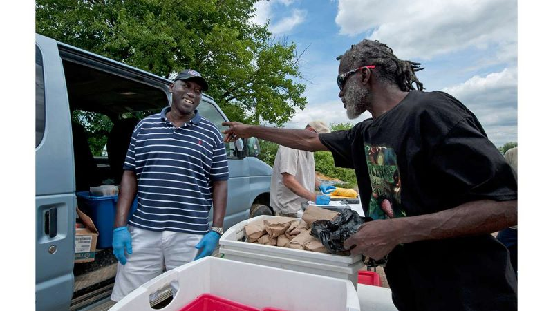 At the needle-exchange van in Camden in 2014, HIV-prevention team leader Sam Myers (left) talks with Nicholas Brown, who is exchanging syringes.  (April Saul for WHYY)