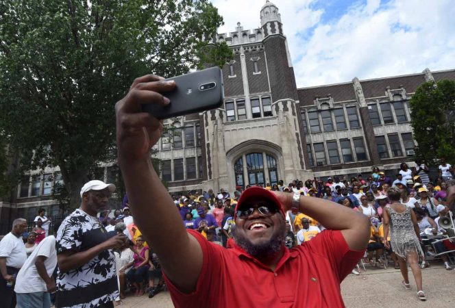 At a June 2017 barbeque to honor Camden High, alumnus John Royal takes a selfie as others assemble for a group photo.  (April Saul/for Newsworks)