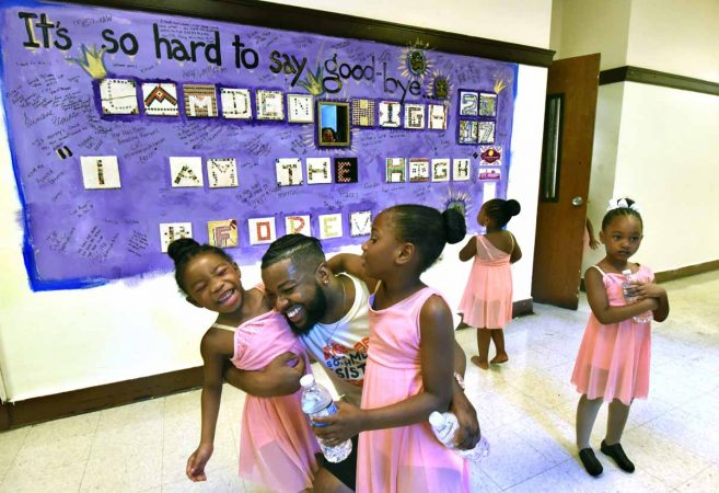 During a June performance at Camden High, members of the Camden Sophisticated Sisters embrace in front of a bulletin board that students used to say goodbye to the school. (April Saul/for Newsworks)