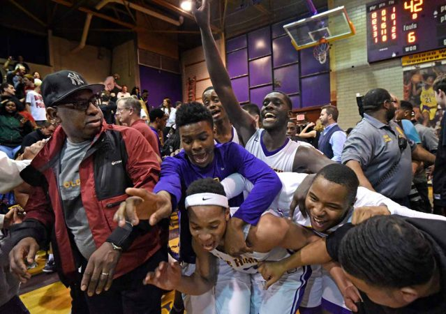 Camden High basketball players exult after a playoff victory against Haddonfield Memorial High School in March 2017; the game was billed as the last ever to be played in the Clarence Turner gymnasium before the school would be demolished. (April Saul/for Newsworks)