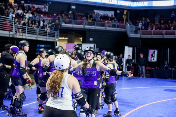 Members of the Rose City Rollers and the new international champions, the Victorian Roller Derby League, hug after the championship game. (Brad Larrison for WHYY)