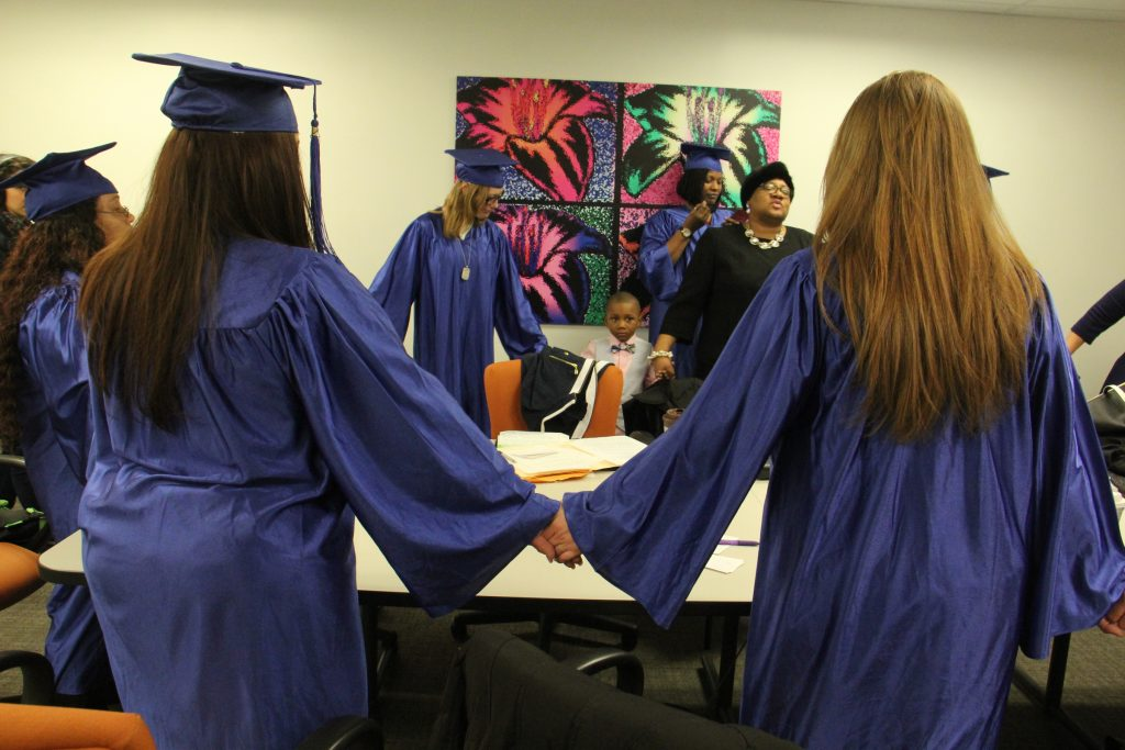 Graduates of the Women Working 4 A Change re-entry program join hands for a prayer before the graduation ceremony held at the Philadelphia school administration building on Feb. 15, 2017.