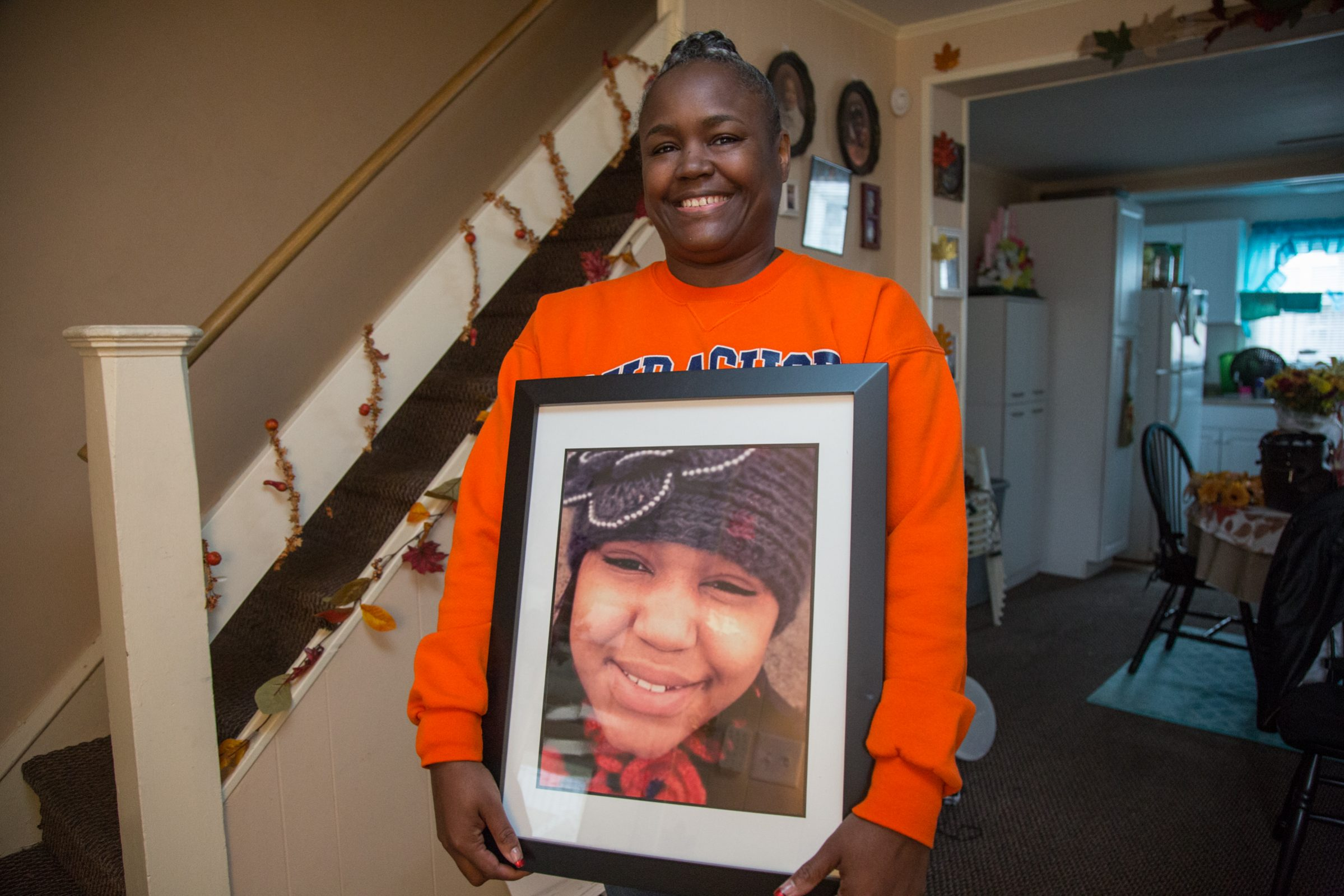 Anita Mason holds a photo of her late daughter, Robin West, in her Upper Darby home.