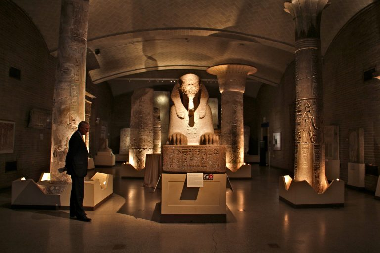 A man looks at a sphinx of red granite in Penn Museum's Egypt gallery