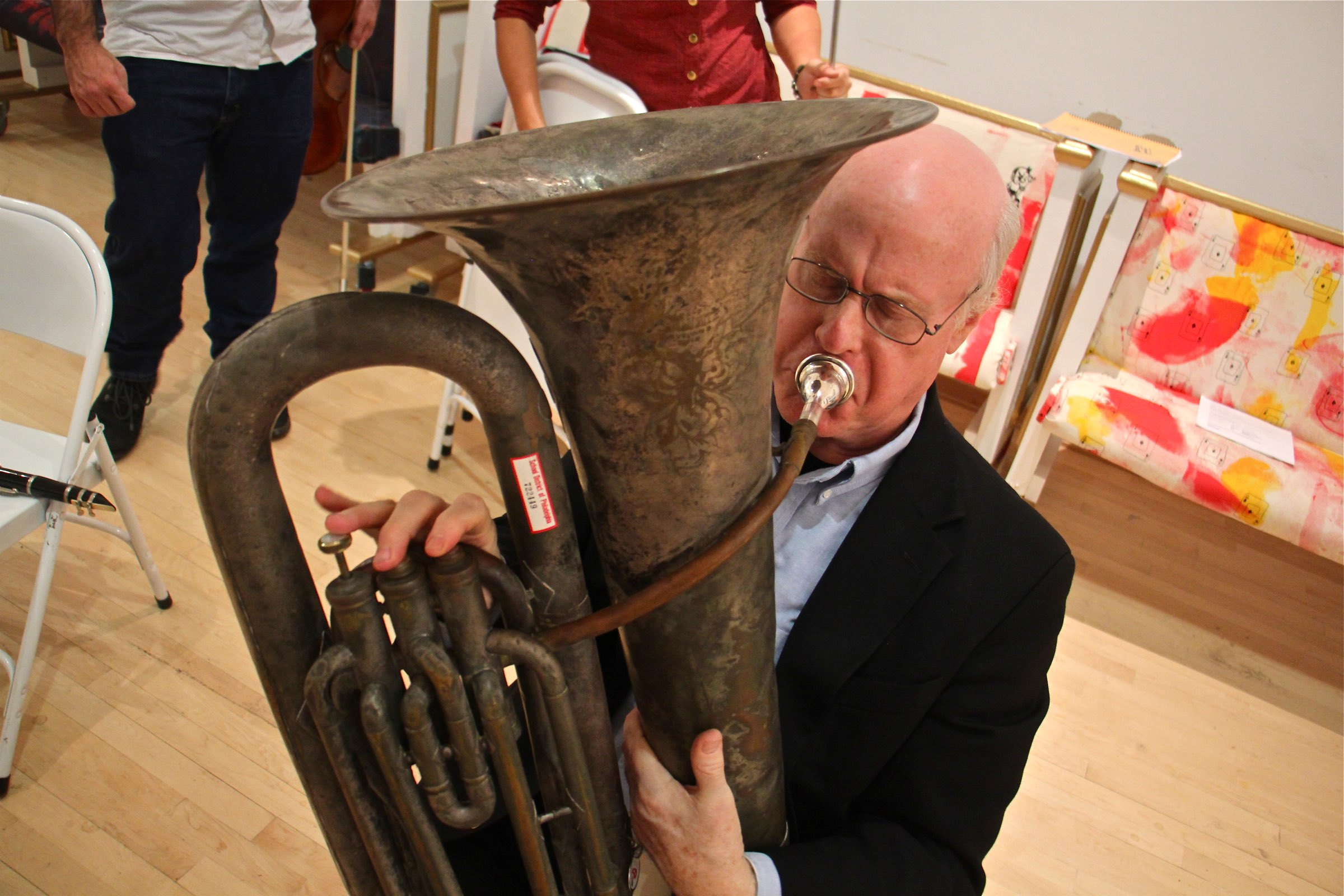 "Temple teacher Jay Krush coaxes music from a broken tuba during a rehearsal for ""Symphony for a Broken Orchestra."""