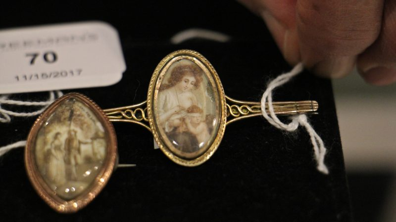 A mourning pin from the late 18th or early 19th century shows a woman blindfolding Cupid. Whether the pin depicted the mourner or the mourned is unknown.