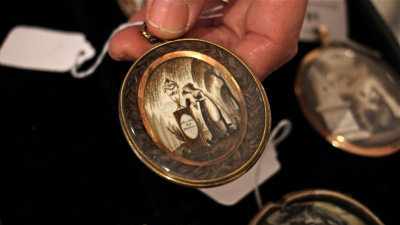A palm-sized oval pendant holds a painting on ivory of a woman grieving beside a gravestone. The image is framed by braided human hair.