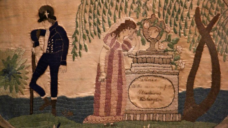 A 19th century embroidered cloth shows a woman grieving at the grave of George Washington.