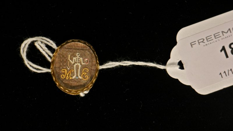 An enameled skeleton holds an hourglass and an arrow in this late 17th century mourning slide. The image is set against intricately woven hair and protected by a faceted rock crystal.