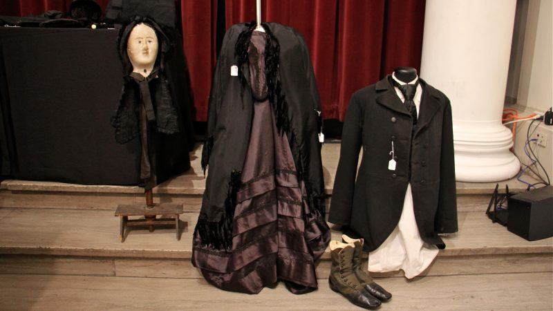 Black formal suit and dress represent mourning clothing of the 19th century.
