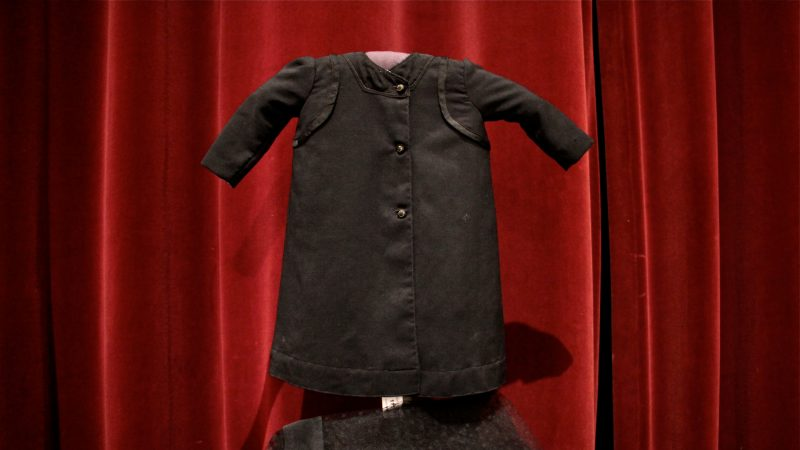A child's black mourning gown stands out against a red velvet curtain