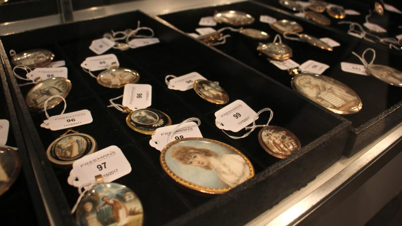 Lockets depicting various emblems of mourning are displayed in a glass case with auction tags attached