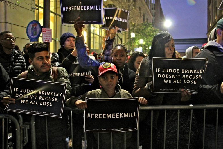 People holding Free Meek Mill signs crowd up to a barrier outside the center for criminal justice