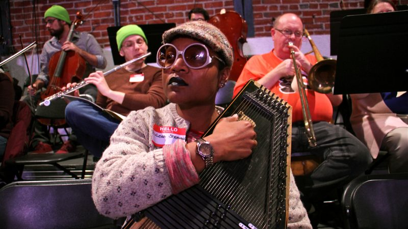 Evelena Shermaine Pinder, who works in Philly's pre-K program, strums a zither during rehearsal for