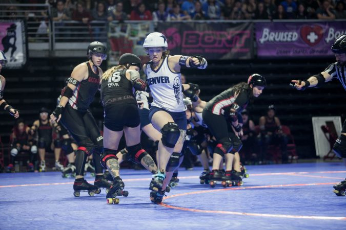 The Gotham Girls Roller Derby team, in black, vie against the Denver Roller Derby Team during the WFTDA International Championship at the Liacouras Center. (Brad Larrison for WHYY)