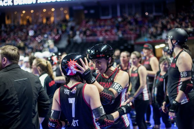 Members of the Gotham Girls Roller Derby Team celebrate winning third place at the WFTDA international Championship at The Liacouras Center Sunday. (Brad Larrison for WHYY)