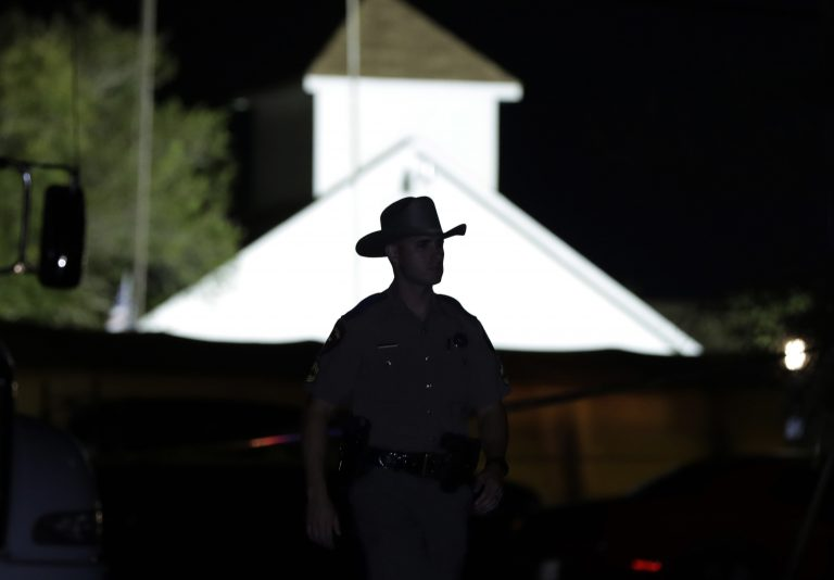 A law enforcement official walks past the First Baptist Church of Sutherland Springs, the scene of a mass shooting, Sunday, Nov. 5, 2017, in Sutherland Springs, Texas.