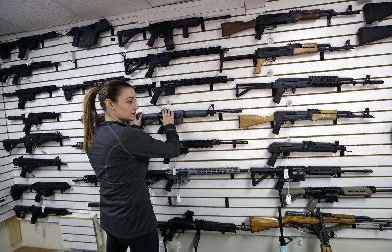Gun shop owner Tiffany Teasdale-Causer returns a Ruger AR-15 semi-automatic rifle, the same model, though in gray rather than black, used by the shooter in a Texas church massacre two days earlier, to it's place on a wall with dozens of other semi-automatic rifles, Tuesday, Nov. 7, 2017, in Lynnwood, Wash. Gun-rights supporters have seized on the Texas church massacre as proof of the well-worn saying that the best answer to a bad guy with a gun is a good guy with a gun. Gun-control advocates, meanwhile, say the tragedy shows once more that it is too easy to get a weapon in the U.S. (Elaine Thompson/AP Photo)