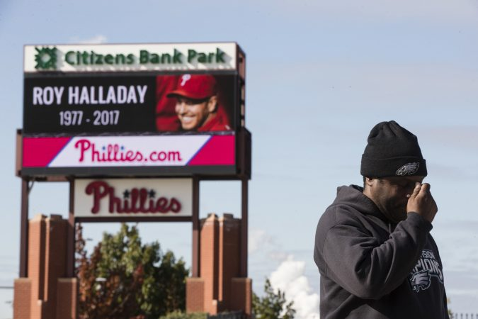 Michael Aikens crosses himself as he pays his respects outside Citizens Bank Park at a makeshift memorial for former Phillies pitcher Roy Halladay in Philadelphia, Wednesday, Nov. 8, 2017. (Matt Rourke/AP Photo)