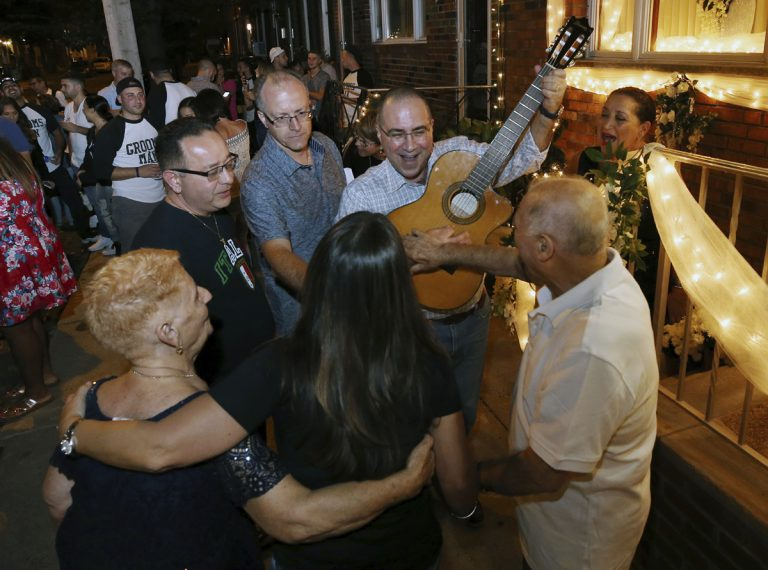 Cousin of the bride, Vincenzo Longo, plays the guitar as a crowd gathers in the street outside the decorated home of Susan and Larry Longo during the Italian wedding serenade for their daughter Stephanie Longo, Saturday, Oct. 7, 2017, in Philadelphia, Pa.  An Italian wedding tradition is alive and well in south Philadelphia, where young couples are transforming something old into something new with their take on the wedding serenade. (Mel Evans/AP Photo)
