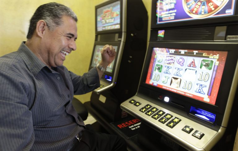 Chino Roberto Vasquez, owner of Chino's Pizzeria celebrates a winning hand on one of the new legal video poker machines, in his restaurant Tuesday, Oct. 9, 2012, in Justice, Ill. (M. Spencer Green/AP Photo)