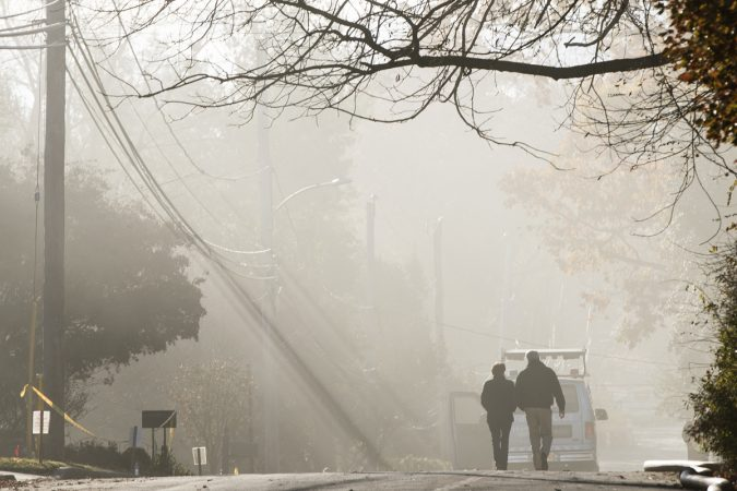 With smoke heavy in the air, a couple walks in the vicinity of a fire at the the Barclay Friends Senior Living Community in West Chester, Pa., Nov. 17. 2017. (Matt Rourke/AP Photo)