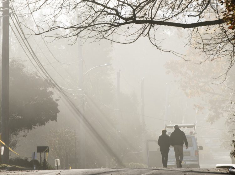 With smoke heavy in the air a couple walks in the vicinity of a fire at the the Barclay Friends Senior Living Community in West Chester, Pa., Friday, Nov. 17, 2017.  At least 20 people have been injured in a massive fire at the senior living community.   (Matt Rourke/AP Photo)