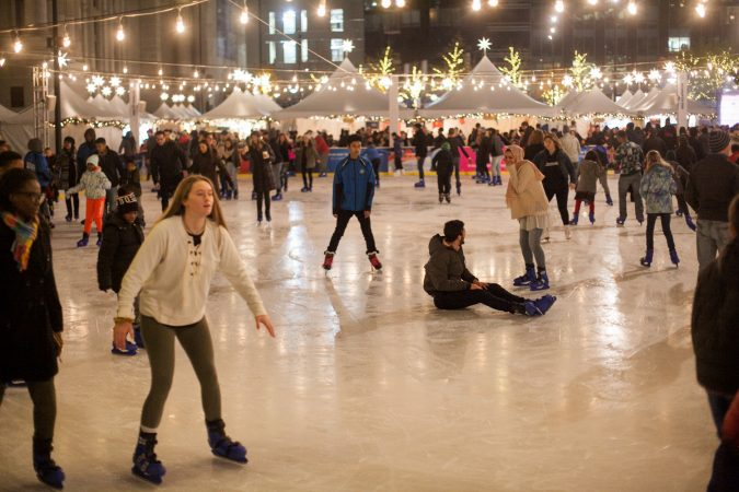 Ice skaters glide around the rink installed at Dilworth Park Friday evening during the Christmas tree lighting ceremony and opening of the Christmas Village. (Brad Larrison for WHYY)